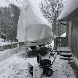 Båten står trygt på stativet sitt og snøfreseren holder det fritt for snø rundt den.